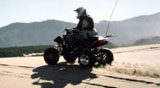 Bob riding our black 400cc LTZ Suzuki quad against a sunny dune crest on a winter morning